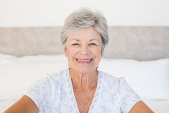 Happy senior woman sitting on bed Royalty Free Stock Photos