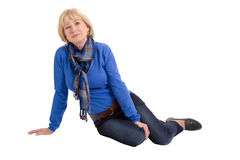 Happy senior woman sitting on floor isolated on white background Royalty Free Stock Photo