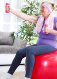 Happy senior woman sitting on gym ball, and exercise with dumbbe Royalty Free Stock Photo