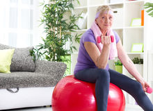 Happy senior woman sitting on gym ball, and exercise Stock Photo