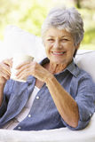 Happy Senior Woman Sitting On Sofa With Drink Royalty Free Stock Images