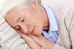 Happy senior woman sleeping on pillow at home Royalty Free Stock Image