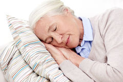 Happy senior woman sleeping on pillow at home Royalty Free Stock Photos