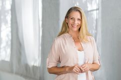 Happy senior woman smiling. Happy senior woman in smart casual looking at camera. Cheerful mature woman standing and smiling indoor. Portrait of satisfied and stock photo