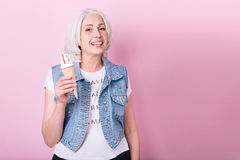 Happy senior woman smiling and holding an icecream. Stock Photo
