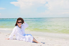 Happy active senior woman. A smiling senior woman in a sun hat and sunglasses on beach royalty free stock photo