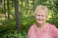 Happy senior woman. A smiling 75 year old senior woman standing outdoors royalty free stock photos