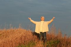 Happy mature woman with spread arms in nature. Happy senior woman spread her arms, standing in brown grass in nature in front of blue sky stock photos