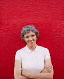 Happy senior woman standing against red background Royalty Free Stock Photo