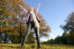 Happy senior woman standing in autumn field with arms raised Royalty Free Stock Image