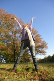 Happy senior woman standing in autumn field with arms raised stock photo