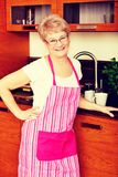 Happy senior woman standing in kitchen royalty free stock photography