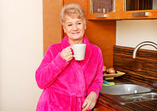 Happy senior woman standing in kitchen and drinking coffee or tea Stock Image