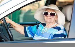 Happy senior woman in sunglasses and hat driving automobile Royalty Free Stock Photography