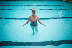 Happy senior woman swimming in pool Stock Images