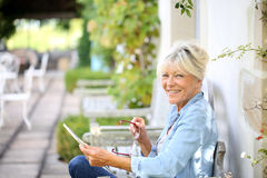 Happy senior woman with tablet outdoors royalty free stock photos