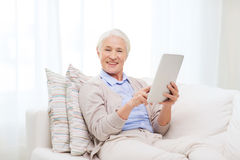 Happy senior woman with tablet pc at home Stock Images