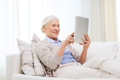 Happy senior woman with tablet pc at home Royalty Free Stock Photo
