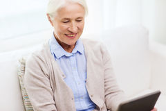 Happy senior woman with tablet pc at home Royalty Free Stock Photos