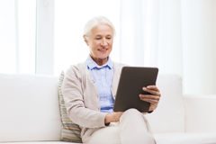 Happy senior woman with tablet pc at home Stock Image