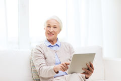 Happy senior woman with tablet pc at home Stock Photos