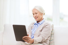 Happy senior woman with tablet pc at home Royalty Free Stock Images