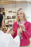 Happy senior woman taking glasses from optician in store Stock Images