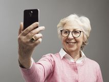 Happy senior woman taking selfies with her smartphone royalty free stock photos