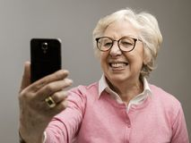 Happy senior woman taking selfies with her smartphone. She is smiling and posing stock images