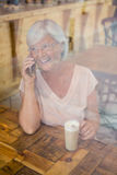 Happy senior woman talking on mobile phone while having cold coffee Stock Image