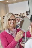 Happy senior woman trying on glasses while optician holding hand mirror Stock Images