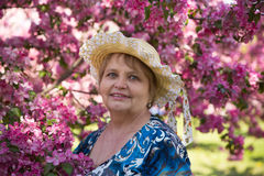 Happy senior woman under pink flowers in summer. Happy senior woman wearing a hat under pink flowers in summer Royalty Free Stock Photos