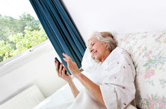 Happy senior woman using cell phone in bed at home Royalty Free Stock Images