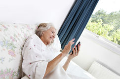 Happy senior woman using cell phone in bed at home Stock Image