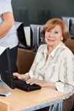 Happy Senior Woman Using Computer At Desk In Classroom Stock Photos