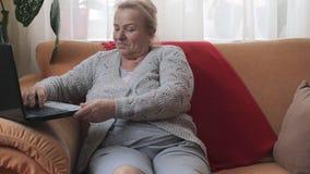Happy senior woman using computer sitting on sofa. Happy senior woman using computer at home sitting on sofa stock footage