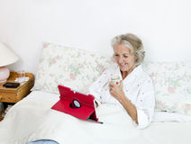 Happy senior woman using digital tablet while having coffee on bed at home Royalty Free Stock Images