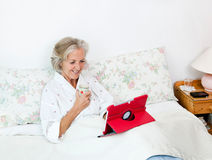 Happy senior woman using digital tablet while having coffee on bed at home Royalty Free Stock Photo