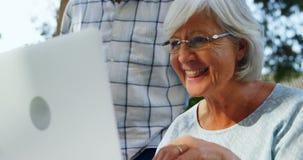 Happy senior woman using laptop in garden 4k. Close-up of happy senior woman using laptop in garden 4k stock footage