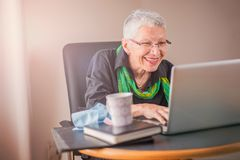 Senior woman browsing internet. Happy senior woman using laptop to browse internet and amuse herself with funny content Stock Photos