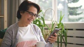 Happy senior woman is using smartphone sitting on sofa at home. Happy senior woman is using smartphone sitting on sofa at home, attractive lady in eyeglasses is stock footage