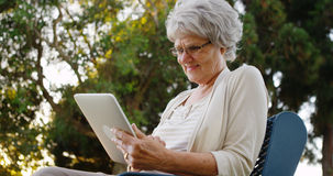 Happy senior woman using tablet at the park Stock Images