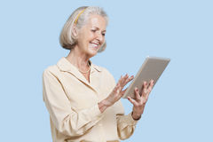 Happy senior woman using tablet PC against blue background Royalty Free Stock Photo