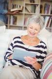 Happy senior woman using tablet while sitting on sofa Royalty Free Stock Photo