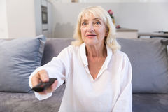 Happy senior woman watching tv and changing channels. With remote control while sitting on a couch at home Royalty Free Stock Photo