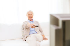 Happy senior woman watching tv at home. Family, technology, television, age and people concept - happy senior woman watching tv at home Royalty Free Stock Photography