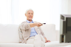 Happy senior woman watching tv at home. Technology, television, age and people concept - happy senior woman watching tv and changing channel with remote control Royalty Free Stock Image