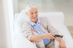 Happy senior woman watching tv at home. Technology, television, age and people concept - happy senior woman watching tv and changing channel with remote control Royalty Free Stock Photography
