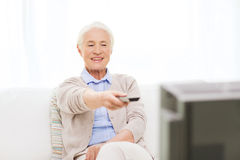 Happy senior woman watching tv at home Royalty Free Stock Image