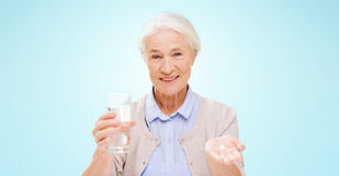 Happy senior woman with water and medicine Stock Images